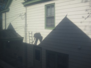 Roofer shadow on the neighbor's house.